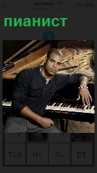 сидит около пианино мужчина музыкант и готовиться играть