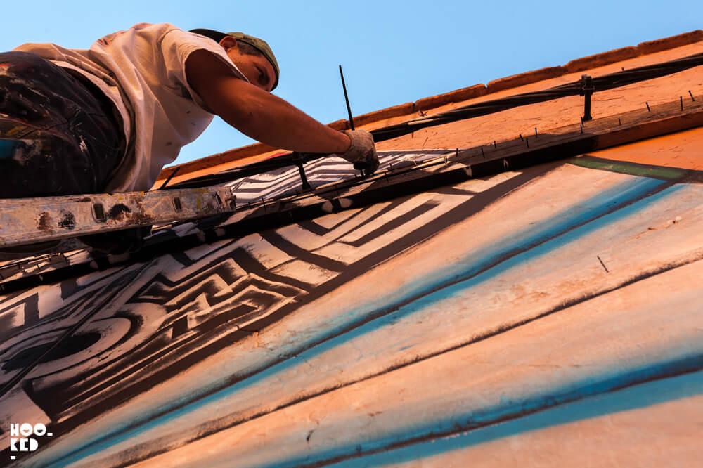 Street Artist Giacomo Bufarini aka RUN at work on a mural in Marrakech, Morocco