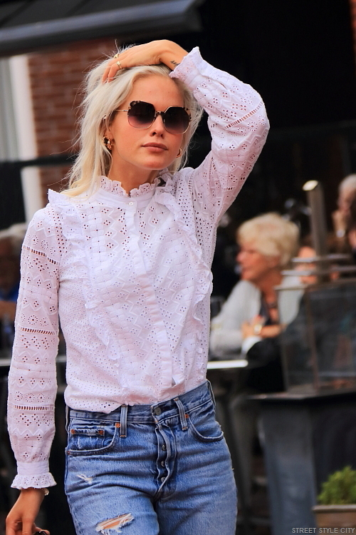 Beautiful dutch blond girl wearing white lace top and her jeans in the street. Streetstyle fashion.
