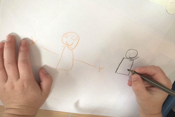 child drawing people with black skin and white skin