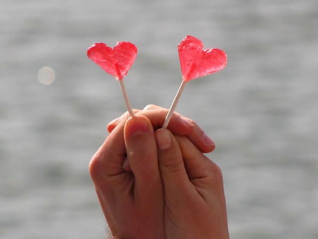 Sobre Relacionamentos Descartáveis - a imagem exibe duas mãos segurando juntas pirulitos em forma de coração