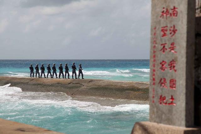 """Fevereiro 2016: soldados chineses nas ilhas Spratly (Nansha para a China) . A placa diz: """"Nansha é nossa terra nacional, sagrada e inviolável""""."""