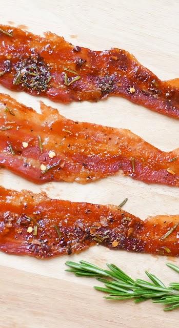 bacon on a wooden cutting board with fresh rosemary garnish.