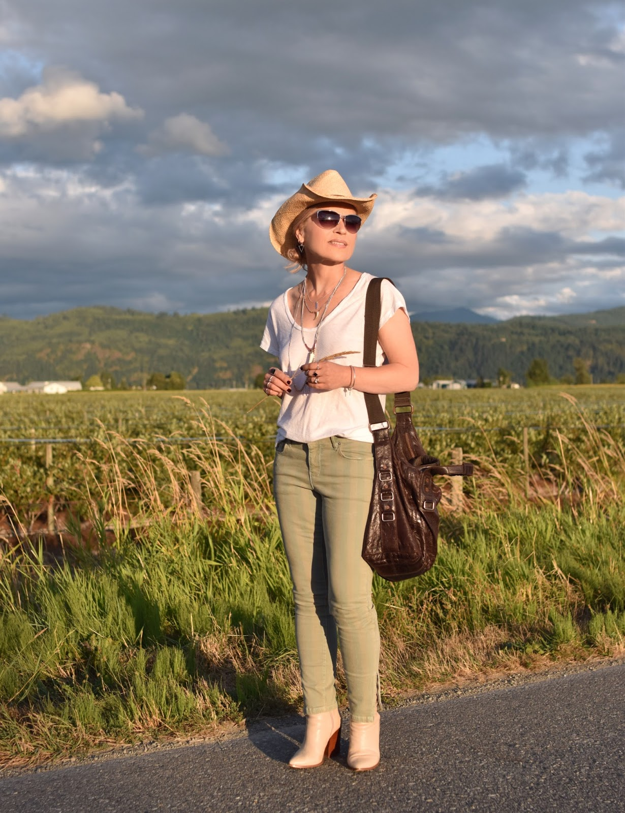 Farm fresh:  green striped skinny jeans, slouchy tee, ivory booties, and a cowboy hat