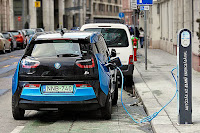 A BMW electric vehicle at a road-side charging station in Budapest, Hungary. (Credit: Albert Lugosi/Wikimedia Commons) Click to Enlarge.
