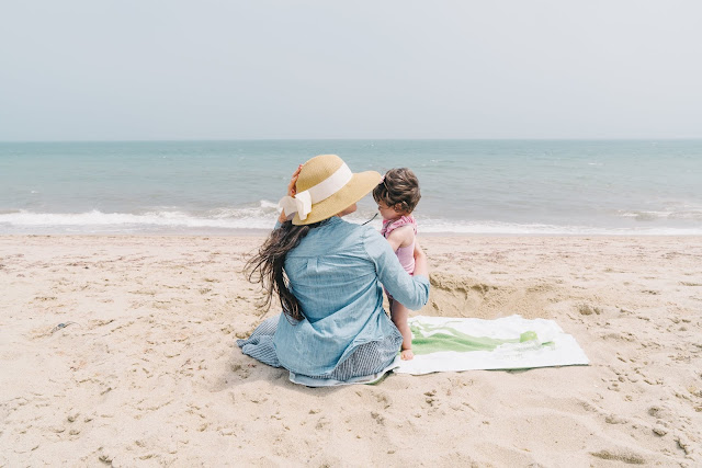mother and daughter on a blanket at the beach