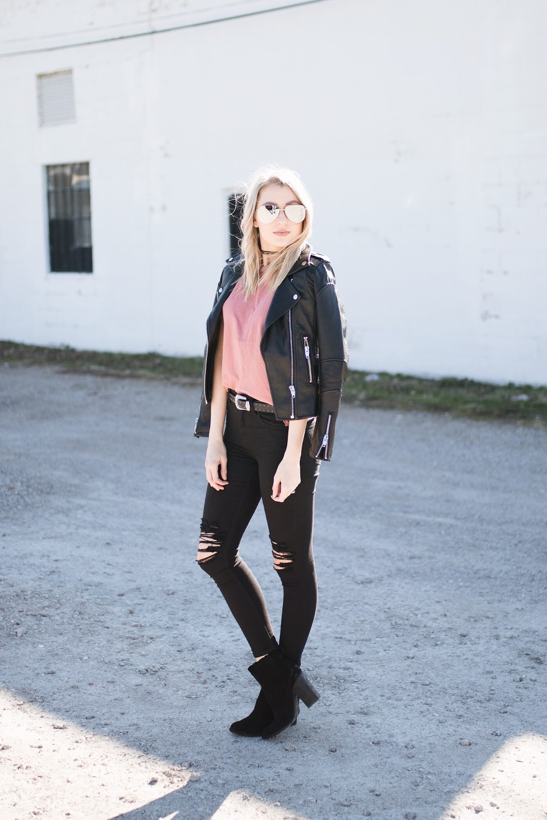 Edgy winter outfit // faux leather jacket draped over a tee and distressed jeans