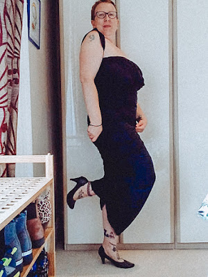 Sarah is wearing a black dress she is stood side on to the camera smiling and has one foot raised she is also wearing black heels