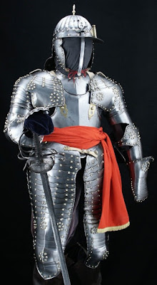 A suit of silver-colored armor with brass studs, some arranged in rosettes; the overlapping plates do not extend past the knees, and the face is uncovered apart from a brim above the eyes. Armor is accessorized with a red sash and a basket-hilt rapier.