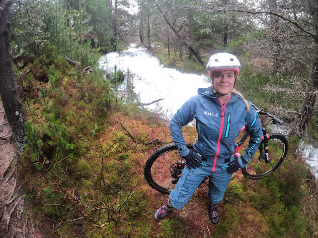 woman in dirtlej dirtsuit standing near water fall with mountain bike and dog