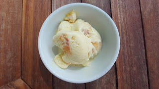 bowl of peach ice cream on a wooden table