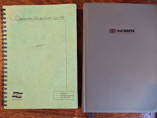 Notebook on the left reads Dementia Adventure, notebook on the right reads Neil Mapes
