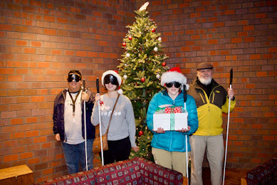 Dan Burke and Colorado Center for the Blind students Cristian, Shyanne, Kelly,  beside the Christmas Tree while delivering treat to City of Littleton offices