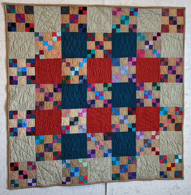 A scrap quilt with small nine-patches alternate with red, cadet blue, or tan solid squares are quilted with a variety of free motion designs.
