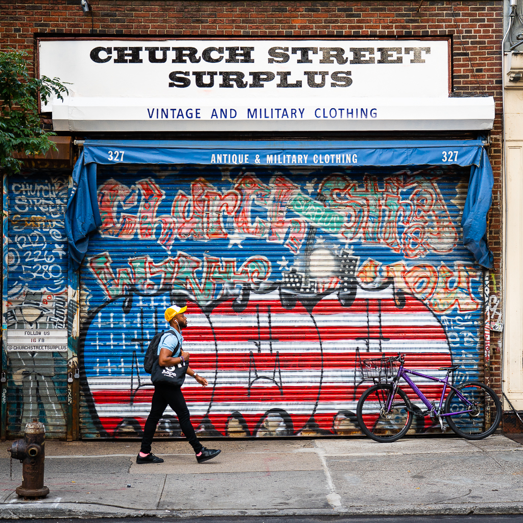 a photo of an army surplus store with graffiti on church street in new york city