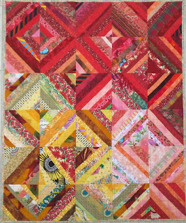 Strings of scrap fabric in red and yellows are sewed diagonally to make blocks for this quilt