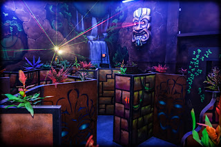 a tiki mask shoots lasers amid barriers and tropical decor in the Galaxy Gaming laser tag arena in Sioux Falls, South Dakota