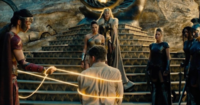 ID: a scene from the 2017 film Wonder Woman. The titular character is standing on steps with her mother behind her. In the foreground, a male soldier is wrapped by a glowing gold rope which a character to his left is holding. The rope is known as the Lasso of Truth.