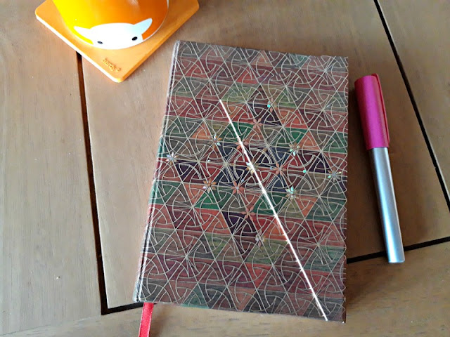 A photo of a pale oak wooden table with an orange mug, a fountain pen and notebook with an ornate design on it