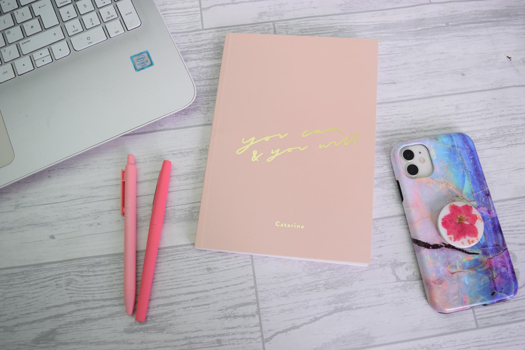 Notebook with pink pens and an iPhone