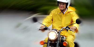 Photo of man in yellow jacket riding a Royal Enfield motorcycle.