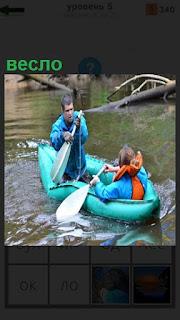 Резиновая лодка им люди с веслами гребут в спасательных жилетах