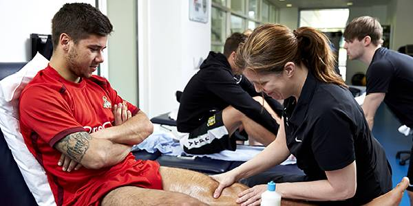 Image of A Football Player Experiences Massage Therapy From a Therapist.