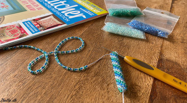 a crocheted blue green and white bead rope in the making with bags of beads in the background and a CrossStitcher magazine