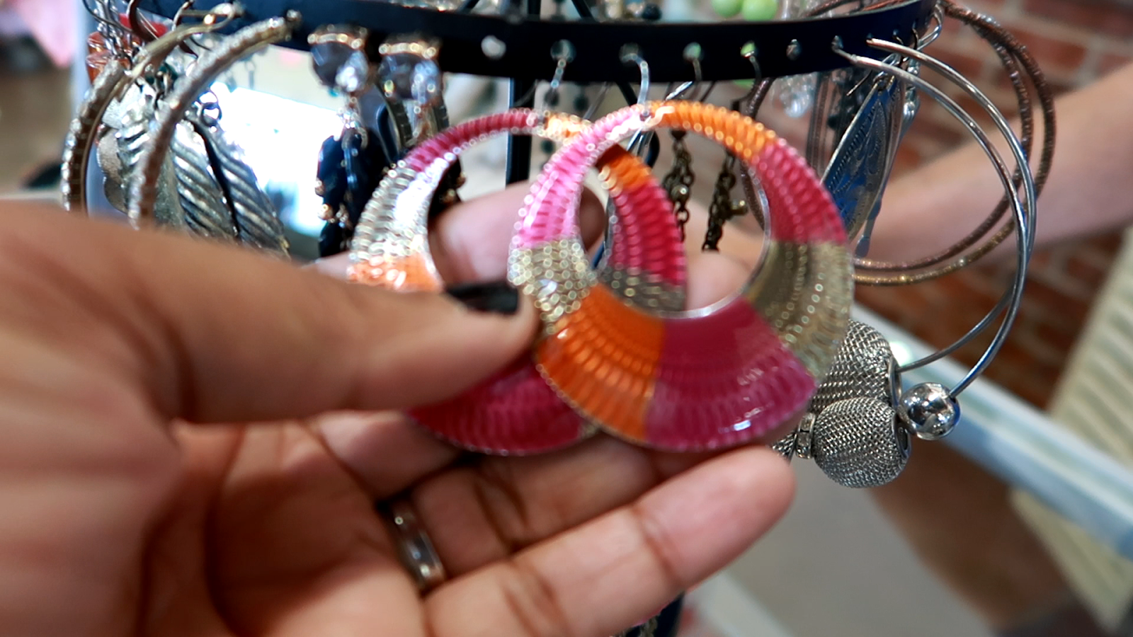 Image: Woman trying on Hippie Earrings at second hand store