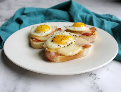 looking across a plate of ham and cheese crostini with fried quail eggs on top
