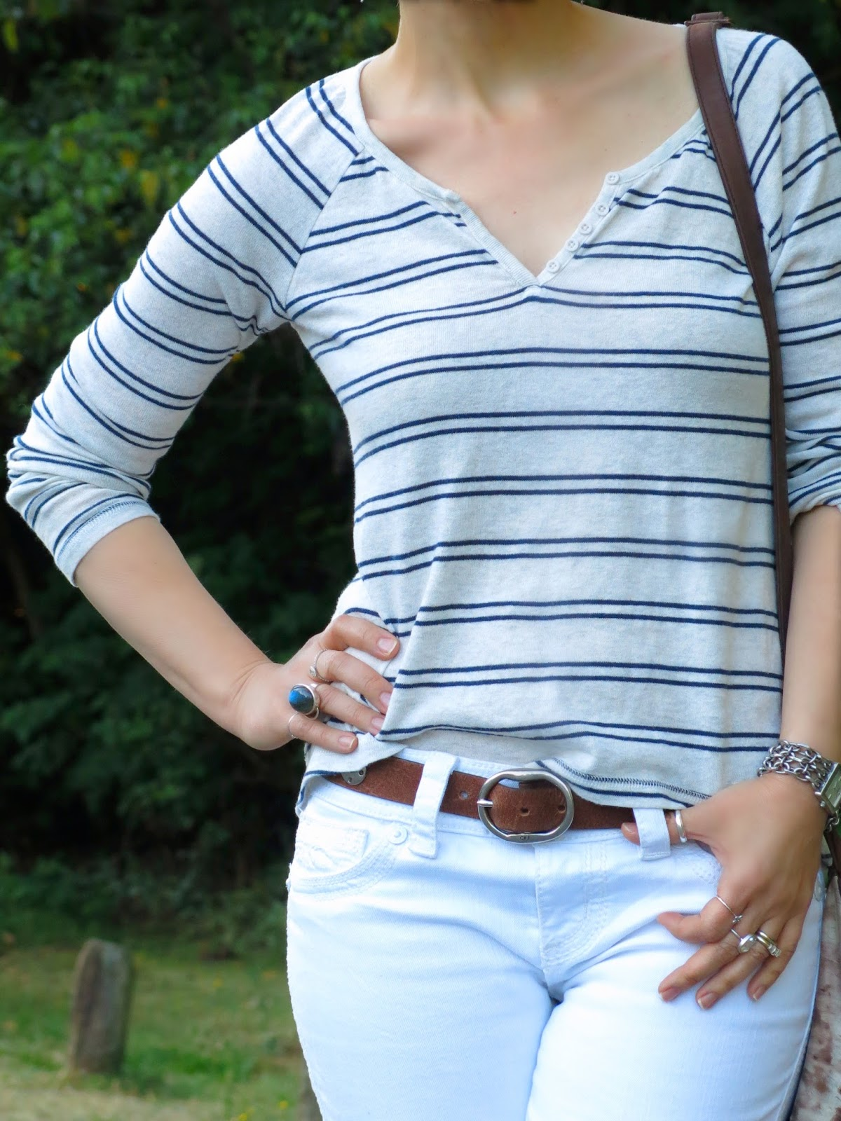 white jeans with a striped henley top, fedora, and accessories