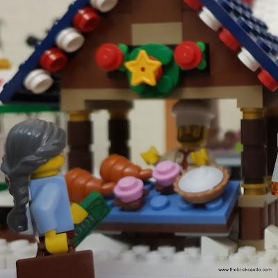 LEGO Winter Village woman walks past bakery
