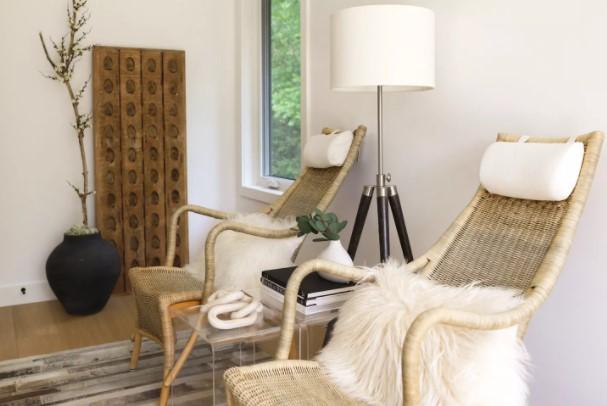 Kursi kayu netral dengan bantal kulit domba palsu di atas di samping lampu dan meja samping dengan buku