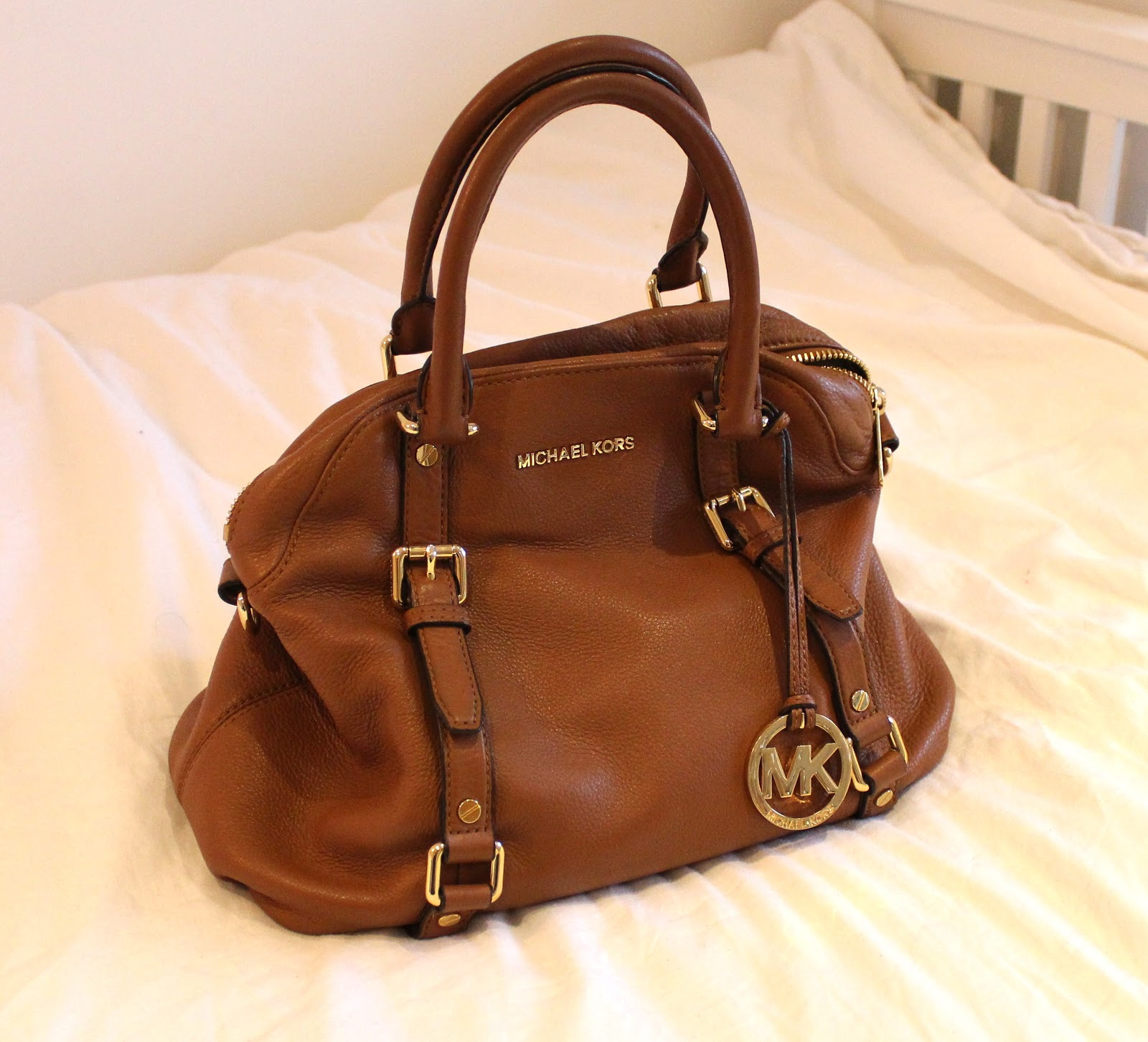 "Some newer bag designs come with the words ""Michael Kors"" attached to the outside of the bag at the top between the straps. The letters are cleanly stamped, evenly coloured and spaced and directly attached to the leather. Unlike Louis Vuitton, Michael Kors bags DO go on sale. I have seen sale bags ."