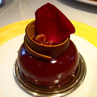 A foto retrata uma escultura de chocolate sobre um prato metalizado redondo apoiado em um sousplat branco com a borda amarela. A base em mousse é composta por uma esfera levemente achatada, sobre a superfície, o reflexo das luzes do teto incidem e deixam-na brilhante. No topo, um rolo deitado que finaliza em curva e em ponta, constituído de duas finas camadas, a parte interna, de massa de nozes com creme e a outra, de pralinê de avelã. No interior do rolo, dois pedacinhos de chocolate partidos na base de uma pétala de rosa vermelha que enfeita e escora-se em parte do rolo. Esta obra de arte é de um aluno do Bellouet Conseil.