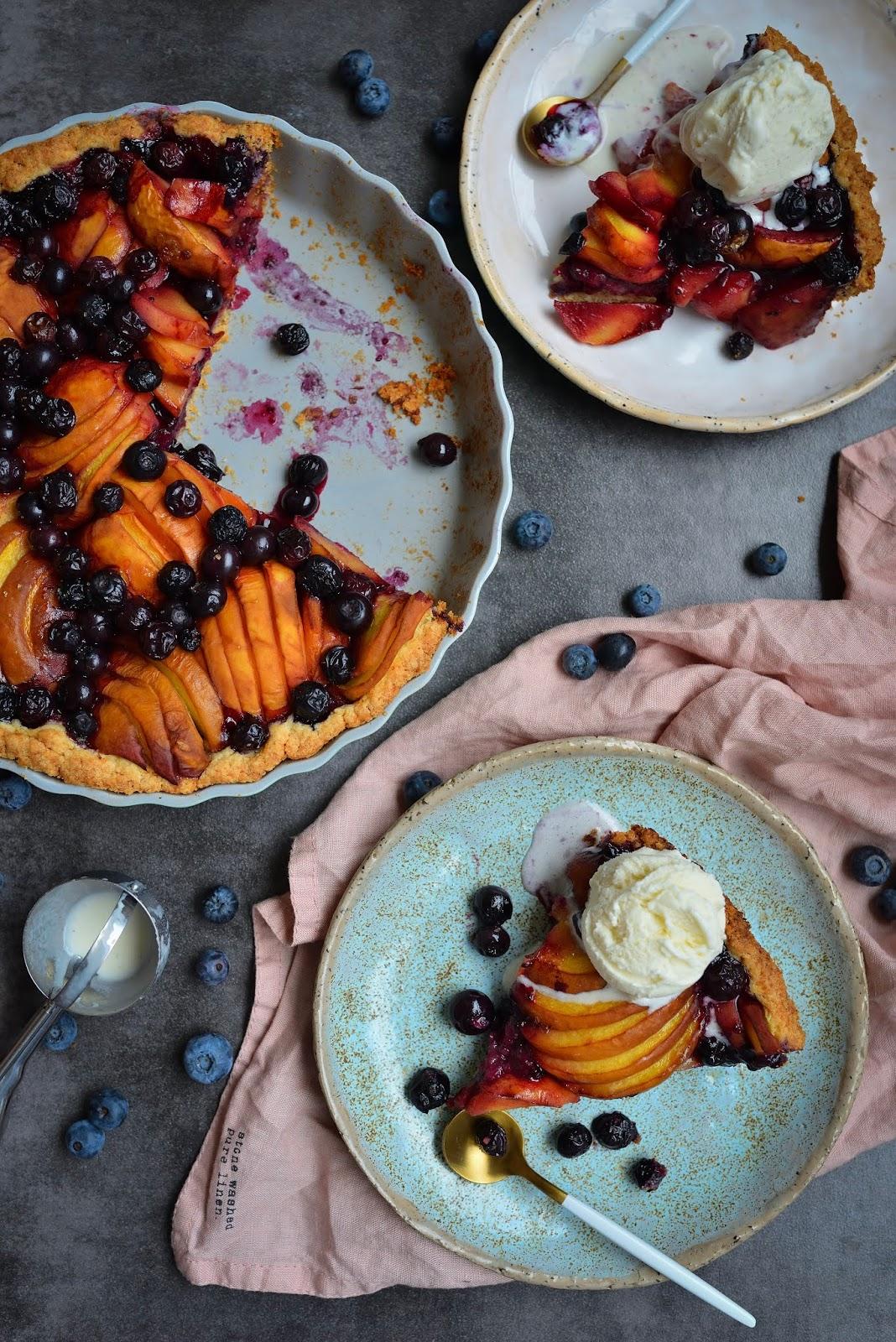 Tarta na kruchym spodzie z brzoskwiniami, borówkami i lodami waniliowymi.