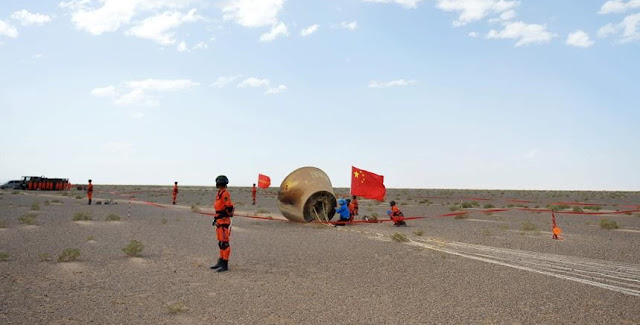 Technical personnel checks the re-entry module in Badain Jaran Desert in north China's Inner Mongolia Autonomous Region, June 26, 2016. Photo Credit: Xinhua/Chen Bin