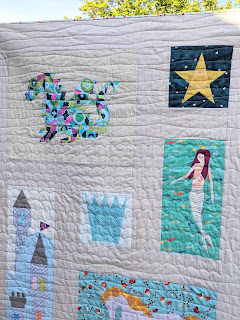 fairytale quilt blocks of a dragon, crown, star and mermaid that are part of the quilt