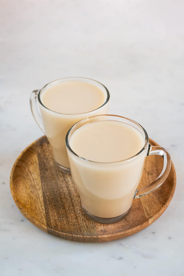 Photo of a couple of cups with homemade oat milk on a round wooden tray