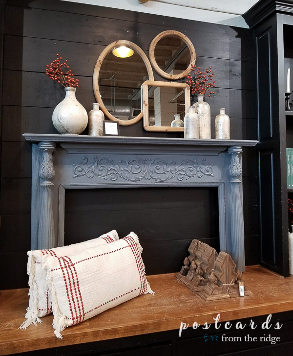 antique mantel with glass jars and wood framed mirrors