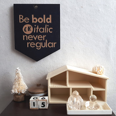 1/12 scale modern miniature tabletop scene in cream and brown containing a tiny bottlebrush Christmas tree, a lidded bowl with gold and white stripes, wooden blocks with the numbers '1' and '5' on them, and an empty dollshouse. Above it on the wall is a wallhanging that says 'Be bold or italic, never regular'