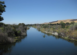 Smooth blue water of Coyote Creek, looking north from the bridge near Metcalf Road, San Jose, California