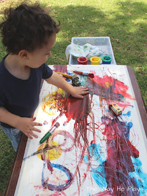 Finger painting on large paper outside