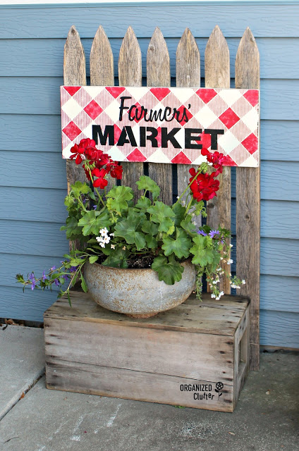 A rustic crate & picket fence outdoor display piece.