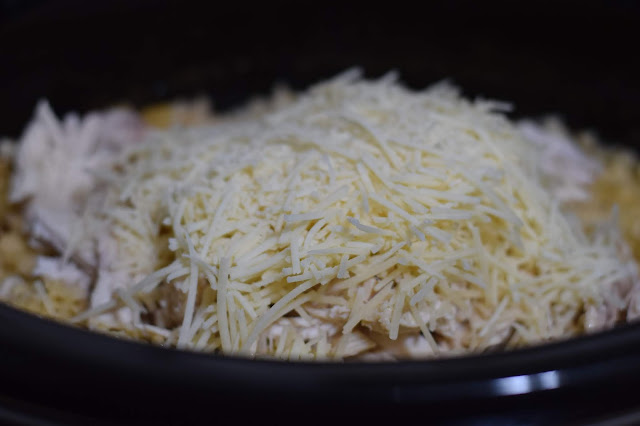 5 oz container of shredded parmesan cheese being added to the crockpot.