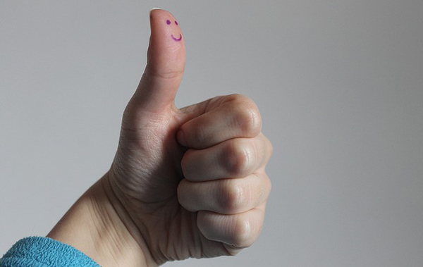 image of a hand, which appears to belong to a white woman, giving the thumbs-up; there is a smiley fce inked onto the pad of her thumb