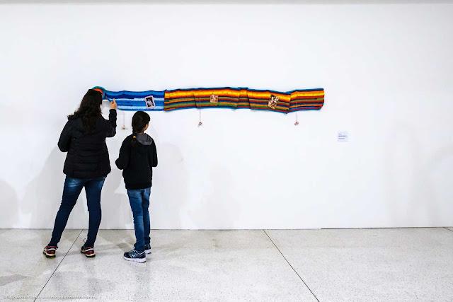 Mulher e menina vendo obra de arte no museu