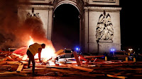 "A protester burns a barricade during ""yellow vest"" riots this month against a gas-tax hike in France. (Credit: Benoit Tessier / Reuters) Click to Enlarge."