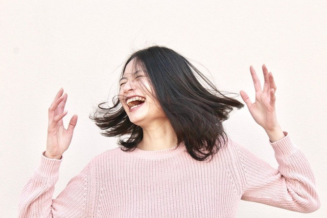 woman in pink shirt laughing happily