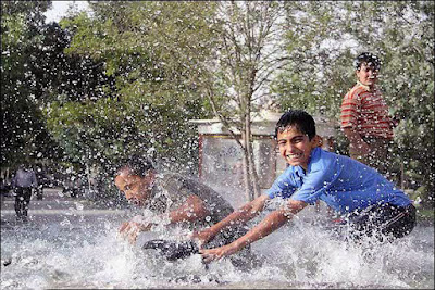 Kids pouring water on each other, Water Festival in Iran